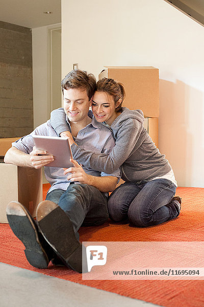 Young couple sitting on floor looking at digital tablet