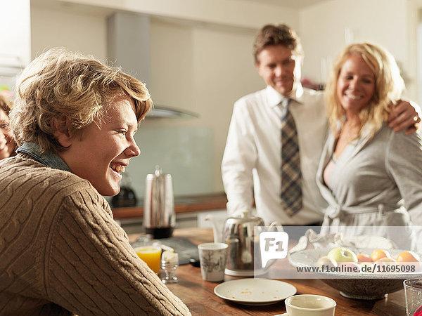 Teenager-Sohn am Küchentisch sitzend mit Eltern im Hintergrund