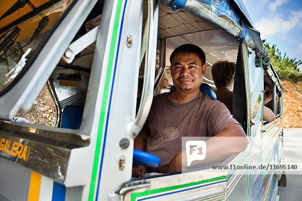 Busfahrer am Fenster lächelnd