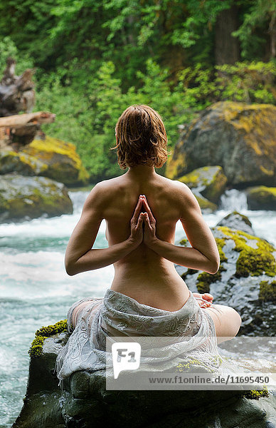Rear view of topless woman meditating on rock by water