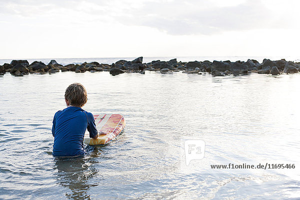 Junge im Meer mit Bodyboard  Kauai  Hawaii  USA