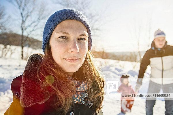 Frau geht mit Familie im Schnee spazieren