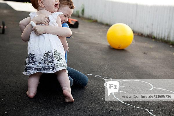 Umarmung von Bruder und Schwester