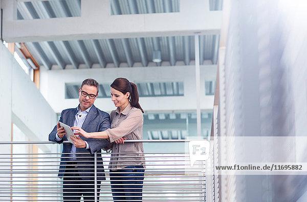Mann und Frau schauen auf das digitale Tablet