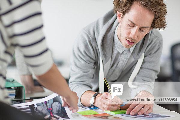 Junger Mann macht Notizen auf dem Schreibtisch im Kreativbüro