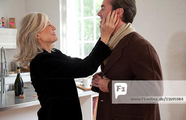 Mann zieht Mantel an  Frau berührt sein Gesicht