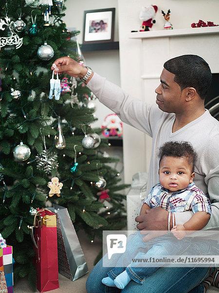 Vater und kleiner Junge schmücken den Weihnachtsbaum