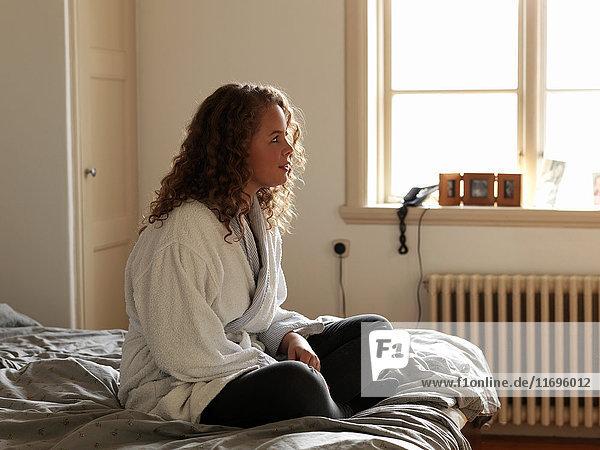 Junge Frau im Bademantel auf dem Bett sitzend