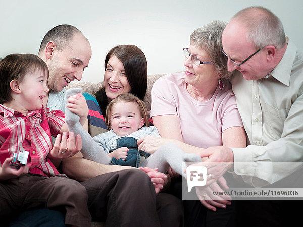 Drei-Generationen-Familie auf Sofa sitzend