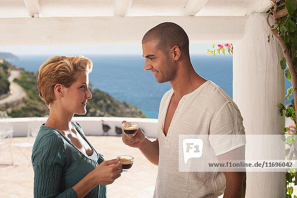 Ehepaar trinkt Kaffee auf dem Balkon
