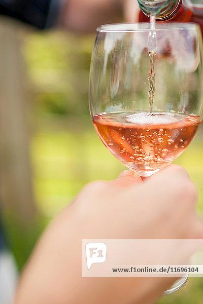 Frau schenkt Glas Wein im Freien ein