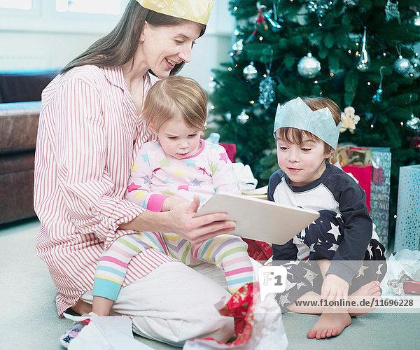 Mutter mit Sohn und Tochter beim Öffnen der Weihnachtsgeschenke