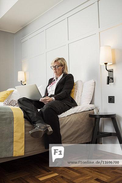 Geschäftsfrau im Bett sitzend mit Laptop an der Wand im Hotelzimmer