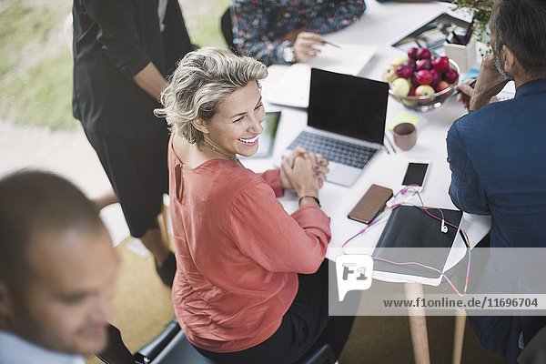 Fröhliche Geschäftsfrau am Schreibtisch mit Kollegen im tragbaren Bürotruck