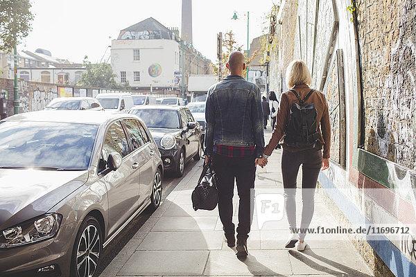 Durchgehende Rückansicht des Paares beim Gehen auf dem Bürgersteig im Stadtverkehr