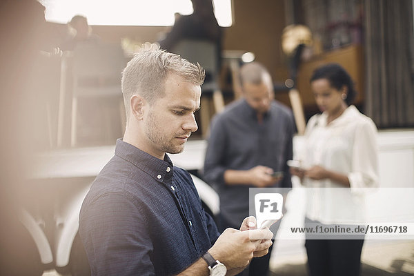 Junger Geschäftsmann mit Smartphone mit Kollegen und tragbarem Bürowagen im Hintergrund
