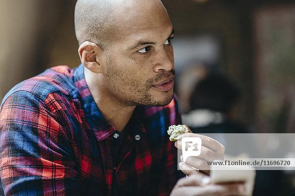 Mittlerer Erwachsener Mann  der Essen hat  während er sein Handy im Coffee Shop hält.