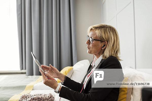 Seitenansicht der reifen Geschäftsfrau mit digitalem Tablett auf dem Bett im Hotelzimmer