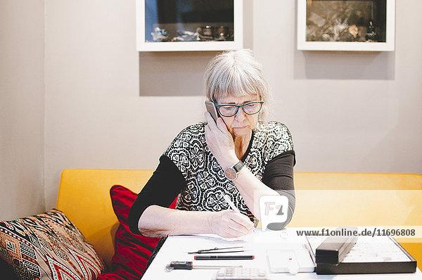 Seniorin beim Telefonieren am Schreibtisch in der Schmuckwerkstatt
