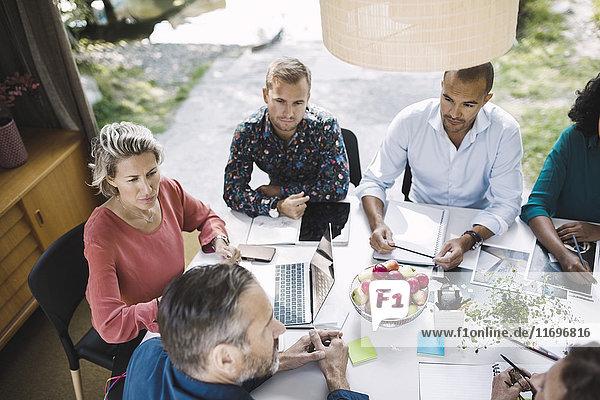 Blickwinkel auf die Planungsstrategie von Geschäftskollegen am Schreibtisch in einem tragbaren Bürowagen