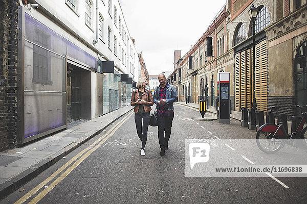 Volle Länge des multiethnischen Paares  das auf der Stadtstraße läuft.