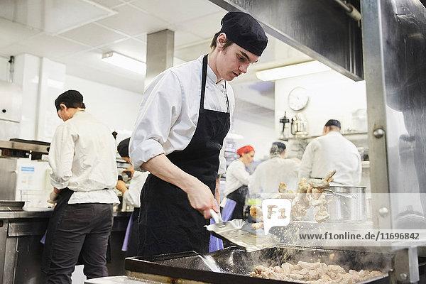 Kochschüler beim Essenswerfen mit Lehrer und Kollegen im Hintergrund in der Kochschule
