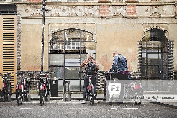 Durchgehende Rückansicht des Fahrradverleihpaares vom Fahrradständer in der Stadt