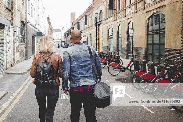 Durchgehende Rückansicht des multiethnischen Paares auf der Stadtstraße