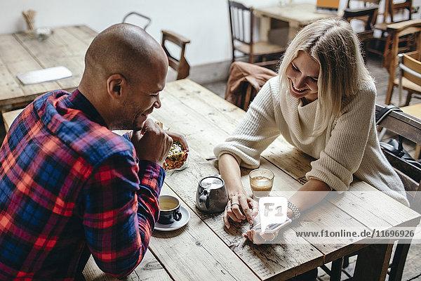 Multiethnisches Paar mit Handy am Tisch im Coffee-Shop