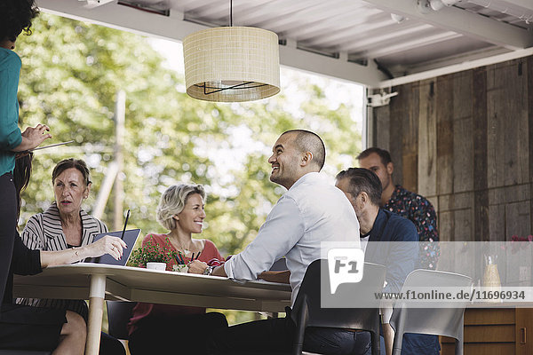 Fröhliche Geschäftsleute diskutieren am Schreibtisch im tragbaren Bürotruck