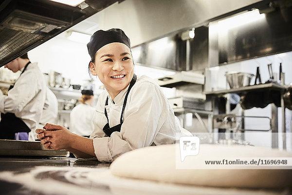 Lächelnde Köchin auf der Theke in der Großküche
