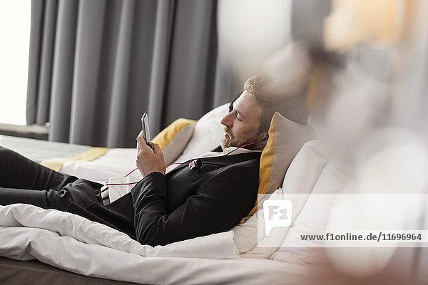 Seitenansicht eines Geschäftsmannes  der Musik hört  während er im Hotelzimmer auf dem Bett liegt.