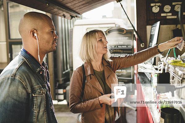 Mittlerer Erwachsener Mann mit Frau beim Kaffeekauf im Speisewagen