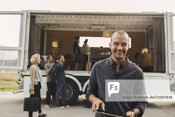 Portrait of smiling businessman holding digital tablet with colleagues and portable office truck on road in background