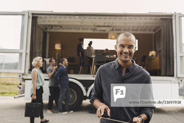 Porträt eines lächelnden Geschäftsmannes  der im Hintergrund ein digitales Tablett mit Kollegen und einem tragbaren Bürowagen auf der Straße hält.