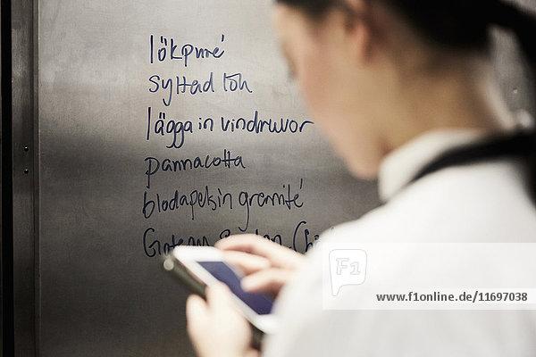 Rückansicht der Köchin mit Handy mit Text auf Metall in der Großküche