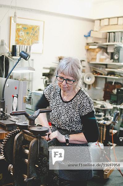 Seniorin beim Bedienen von Maschinen zur Schmuckherstellung in der Werkstatt