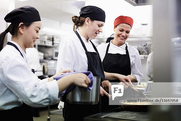 Teacher watching female chef students cooking food in commercial kitchen