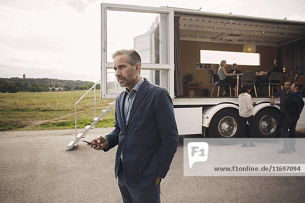 Geschäftsmann hält Handy mit Kollegen und tragbarem Bürowagen im Hintergrund