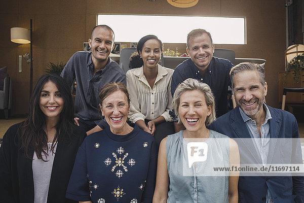 Porträt von lächelnden multiethnischen Geschäftsleuten gegen tragbare Bürofahrzeuge