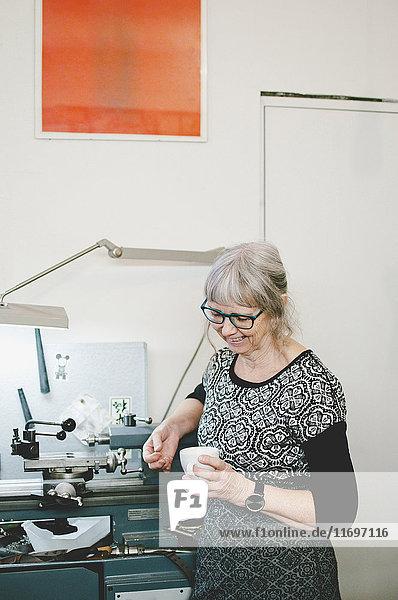 Seniorin lächelt  während sie eine Kaffeetasse in der Schmuckwerkstatt hält.
