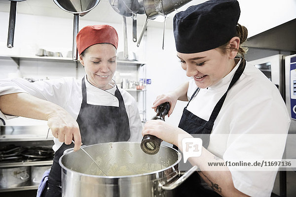 Teacher with female student adding pepper into cooking pan at commercial kitchen