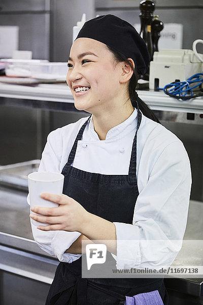 Lächelnde Köchin mit Einwegbecher in der Großküche
