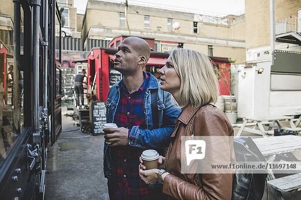 Paar hält Einweg-Coffee-Shop steht vor dem Geschäft
