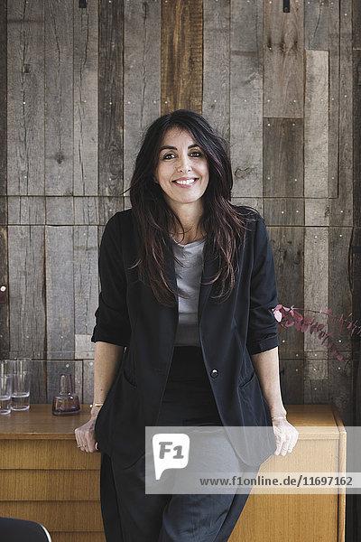 Porträt einer selbstbewussten Geschäftsfrau  die sich auf Sideboard gegen Holzverkleidung in einem tragbaren Bürowagen stützt.