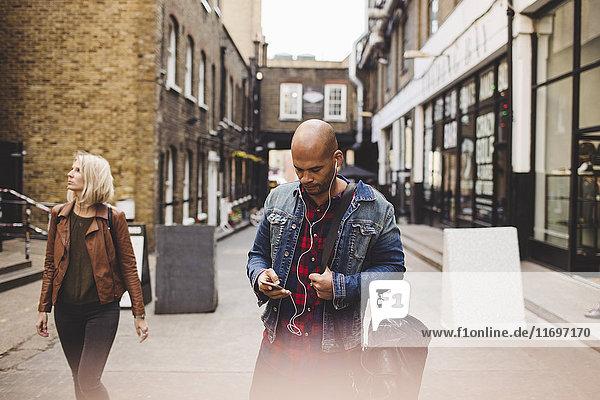 Mittlerer Erwachsener Mann  der Musik über Handy auf der Straße in der Stadt hört.