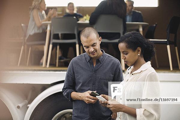 Geschäftsleute  die Mobiltelefone mit Kollegen und tragbarem Bürotruck im Hintergrund benutzen.