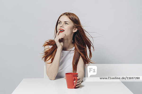 Pensive Caucasian woman sitting at windy table holding red cup