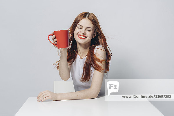 Caucasian woman sitting at windy table holding red cup