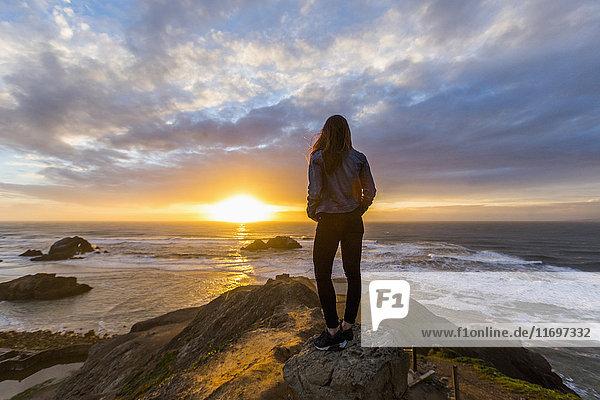 Caucasian woman standing on rock near ocean at sunset
